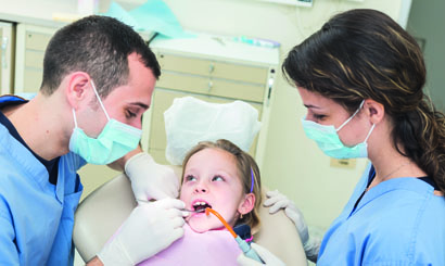 Dentist and Dental Assistant examining Young Girl teeth.