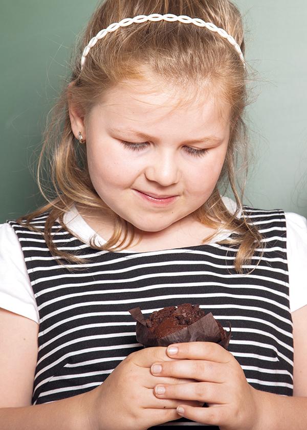 Übergewichtiges Mädchen mit Schoko-Muffin